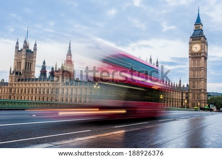 A fast moving double-decker bus crosses Westminster Bridge in London at sunrise. - stock photo