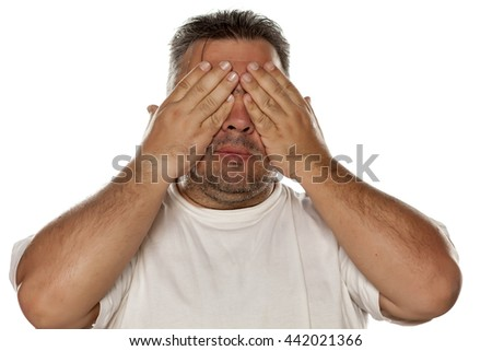 a fat man covering the eyes with his hands