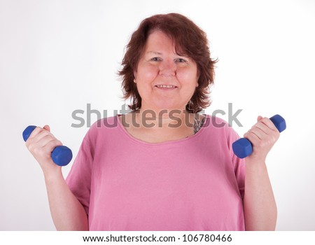 A fat woman is doing exercises with barbells - stock photo