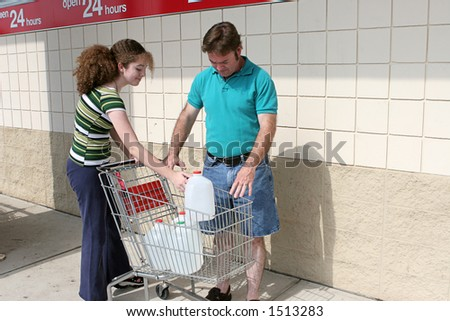 A father and daughter shopping for hurricane supplies.  Their cart is full of water jugs.  Image also appropriate for recycling. - stock photo