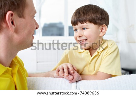 A father and his cute son looking at one another while talking - stock photo
