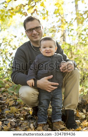 A Father and son playing at park in autumn