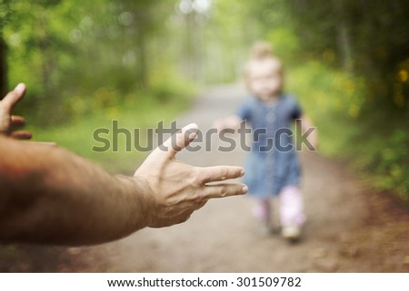 A Father baby walk outside on the meadow - stock photo