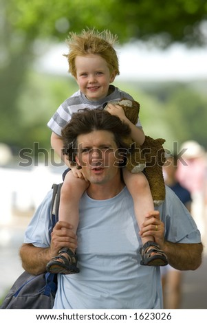 A father carries his son on his shoulders while he in turn carries his favorite toy on a sunny summer day
