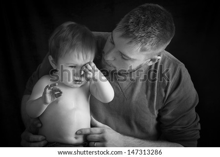 A father comforts his sad son as he holds him on his lap - stock photo