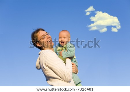 A father hold baby in hands on sunset - stock photo
