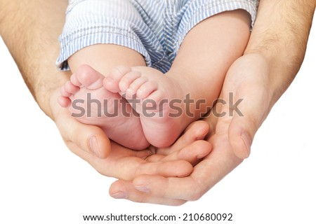 A father hold the feet of his new born son. baby legs - stock photo