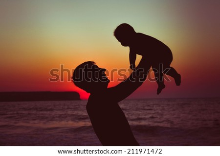 A father holds his child in his arms against the sea. Sunset.  - stock photo