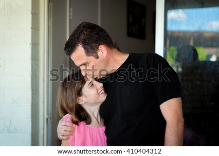 A father kisses his daughter on the forehead as he hugs her and pulls her close. - stock photo