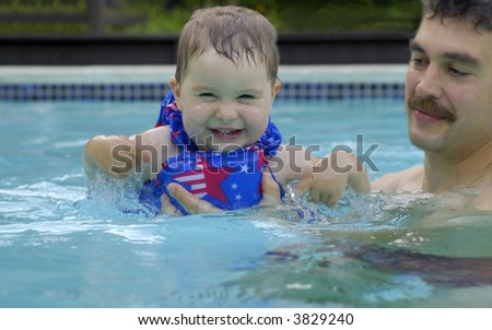 A father watches his toddler daughter in a swimming pool. Focus on the child. - stock photo