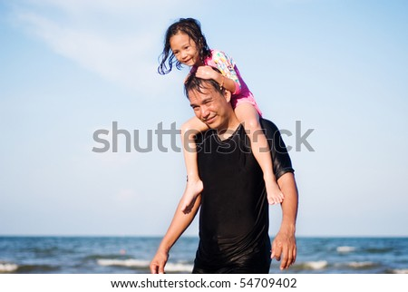 a father with a daughter on the beach - stock photo