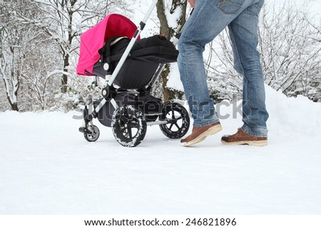 A Father with his Baby in a buggy on a snowy track - stock photo