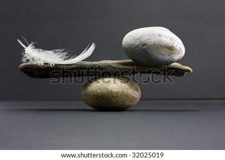 a feather and a stone equally balance - stock photo