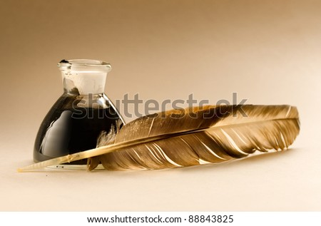 A feather with the bottle full of ink - stock photo