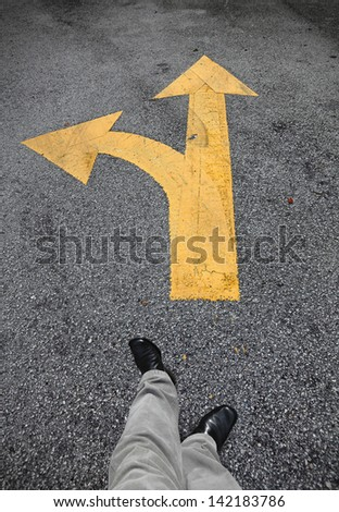A feet walking towards a yellow traffic arrow signage on an asphalt road indicating a detour left turn. - stock photo