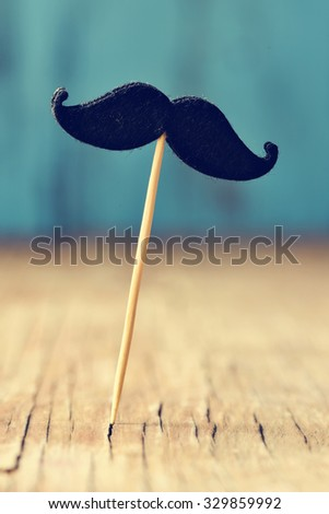 a felt mustache in a stick on a rustic wooden surface - stock photo