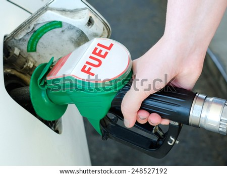 a female arm fuels a car at a gas station - stock photo