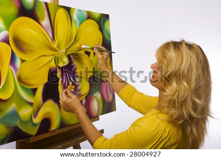 A female artist painting dendrobium orchids on canvas in her studio