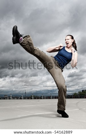 A female athlete performing a turning kick in a dramatic city cloudscape. - stock photo