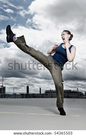 A female athlete performing a turning kick in a dramatic city cloudscape - stock photo