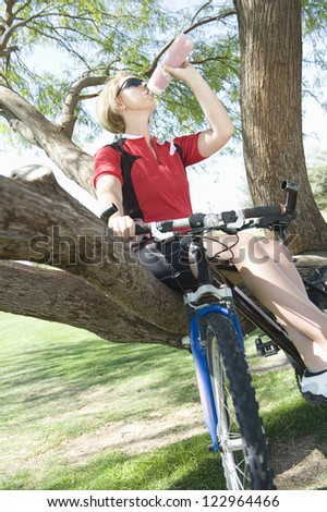 A female bicyclist sitting on tree while drinking water from bottle at park