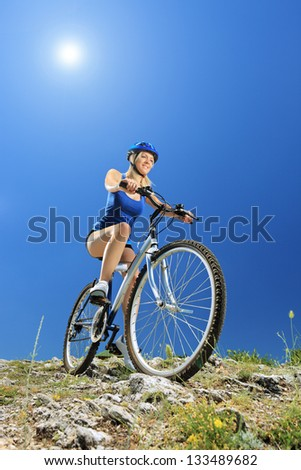 A female biker biking a mountain bike on a sunny day - stock photo