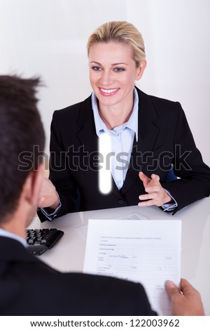 A female business executive smiling at her male colleague. - stock photo