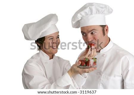 A female chef feeding strawberries to a male chef.  Isolated on white.  Focus on the female chef. - stock photo