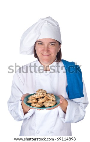A female chef shows off a plate of freshly baked cookies.  Isolated on white for designer convenience.