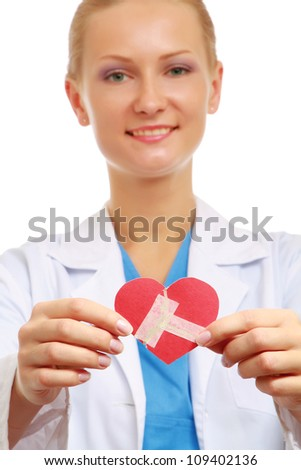 A female doctor holding a wounded paper heart, focus on the heart - stock photo