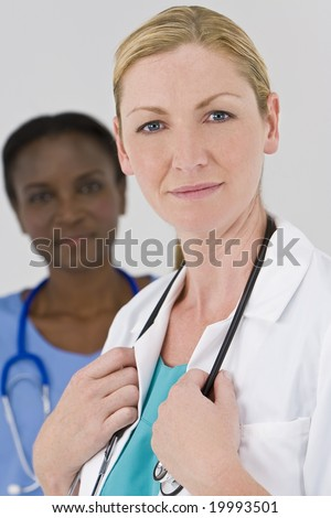 A female doctor with her African American colleague out of focus behind her