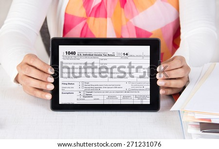 A female employee in her office with a pile of documents shows federal income tax form 1040 in a tablet computer. Concept image for IRS tax e-file system for online tax filing.   - stock photo