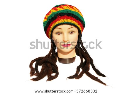 A female Hair Dressers Mannequin Head wears a Rastafarian Hat with Dreadlocks.  Isolated on white with room for your text. - stock photo