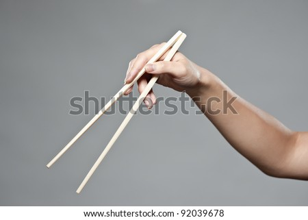 A female hand demonstrating correct oriental chopstick use in open position - stock photo