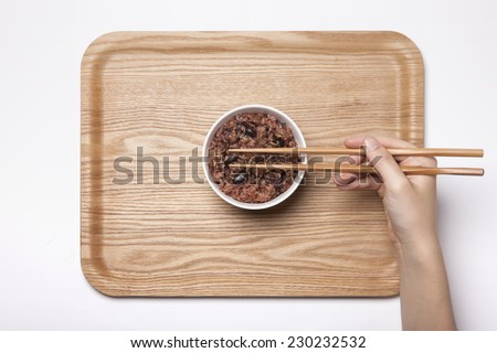 A female hand hold Multi-grain Rice with chopsticks on the wood tray isolated white, top view at the studio. - stock photo