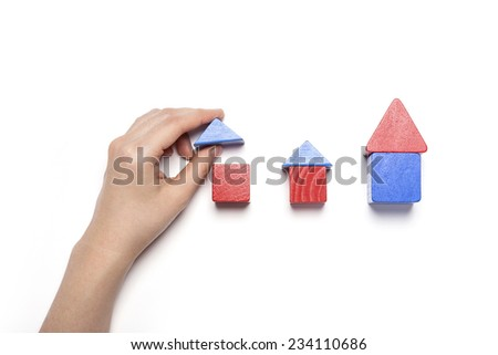 A female hand hold(pick up) blue wood block among the red and blue wood blocks like house(real estate) isolated white, top view at the studio. - stock photo