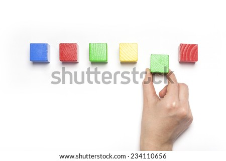 A female hand hold(pick up) green wood block among the color wood blocks isolated white, top view at the studio. - stock photo