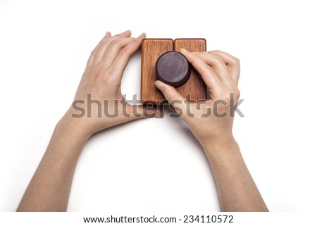 A female hand hold(pick up) the wood block among the wood blocks isolated white, top view at the studio. - stock photo