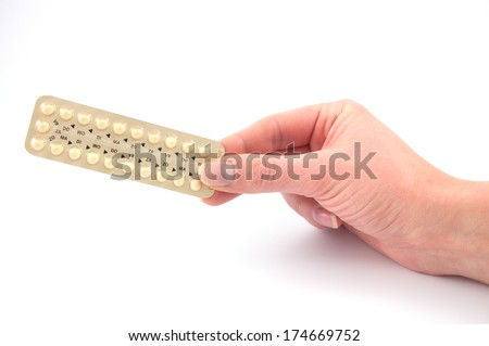 A female hand holds a strip of permanent birth control pills - stock photo