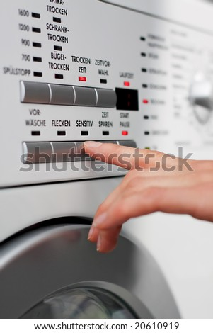 a female hand is pressing a button on a washing machine