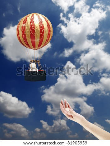 A female hand releasing an exotic colorful stripe balloon with a baby in its basket into a cloudy blue sky. - stock photo