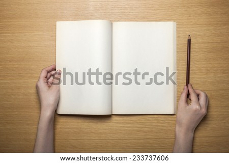 A female hands hold(grip) a vintage(old) book(note, diary) spread on the wooden desk with pencil, top view at the studio. - stock photo
