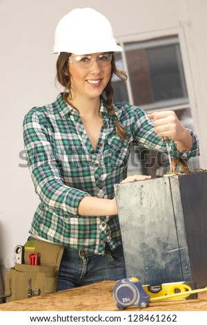 A Female handy with tools works on a repair project in the shop - stock photo