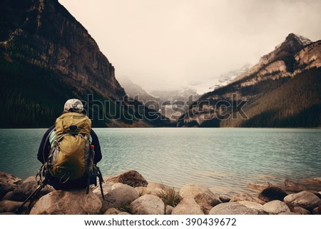 A female hiker at Lake Louise in Banff national park with mountains and forest in Canada. - stock photo