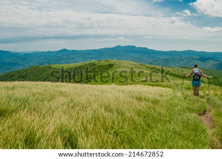 A female hiker pauses on a dirt trail running along a bald mountain range in Tennessee - stock photo