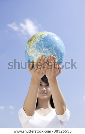 A Female hold the globe over the sky.