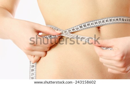 A female is measuring her waist whith measure tape - close-up on white - stock photo