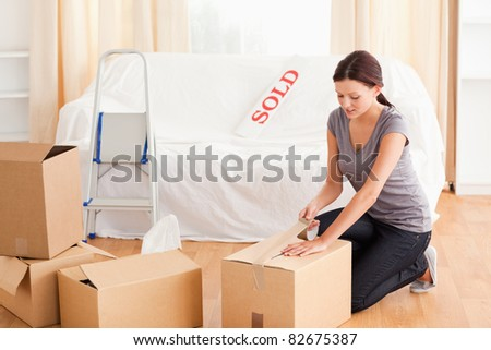 A female is preparing cardboards for the transport - stock photo