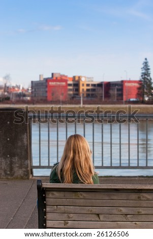 A female model is sitting on a bench while looking across a river at a factory in downtown Portland Oregon. - stock photo
