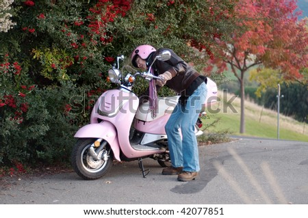 a female motorist parks her scooter next to red berries - stock photo